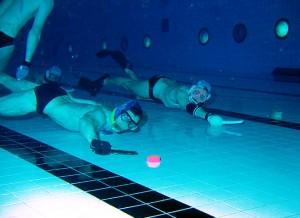 Deux joueurs de hockey subaquatique au fond de la piscine chassant le palet.